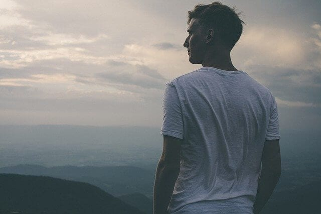 Mężczyzna w białej koszulce w górach